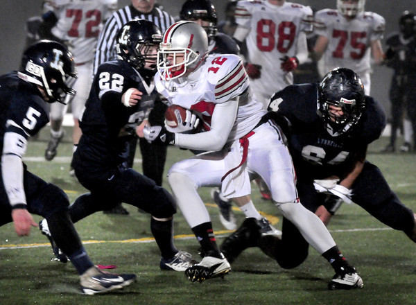 Lowell: Amesbury's Devlin Gobell runs into Lynnfield defenders on a carry. Bryan Eaton/Staff Photo