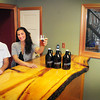 Newburyport: Christian Soucy, brewing apprentice, left, and Alyssa Kirk, sales manager for Riverwalk Brewing Co. show off samples in their tasting room. The production floor can be seen by visitors through the window at right. Bryan Eaton/Staff Photo