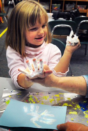 Salisbury: Madelyn Modini, 4, gets her hands covered with paint as she uses them to make snowflakes. The preschooler was in Julie Deschenes class being helped by aide Sonia Stacy. Bryan Eaton/Staff Photo