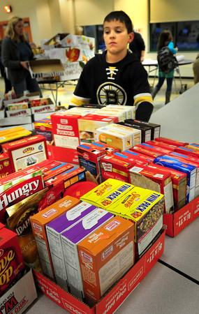 Newbury: Tripp Clark, 10, and other members of the Newbury Elementary School studen council packed boxes of donated food they solicited from the entire school body for Thanksgiving packages for the Pettengill House Food Pantry. They asked for certain items along with a $2 donation that will go toward 75 turkeys and also another 20 for senior citizens. Bryan Eaton/Staff Photo