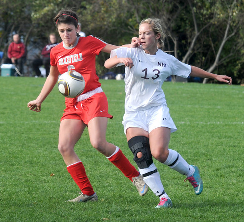 Newburyport: Newburyport's Abigale Muise charges the ball with a Wakefield player during their game at Cherry Hill in Newburyport Sunday. Jim Vaiknoras/staff photo