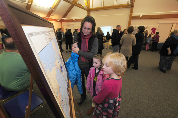 Merrimac: Julei Bethmann and her daughters Emily, 5, and Eliza,8, look at a map containing a pin showing every place a letter or item was recieved by Emma Journeay . They were attending a recieption at the Merrimack Library Thursday night showing some of the many items and letters from around the world sent to Emma , who died this past August on cancer at age nine. . Jim Vaiknoras/staff photo