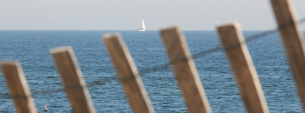 Newbury: A lone sailboat glides by Plum Island on a bight fall day. Jim Vaiknoras/staff photo
