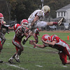 Saugus: Newburyport's Tyler Cusack hurdles a defender during the Clippers game at Saugus Friday afternoon. JIm Vaiknoras/staff photo