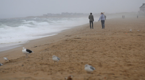 Salisbury: People brave the high surf and rain to walk along Salisbury Beach Sunday morning. Jim Vaiknoras/staff photo