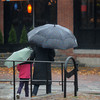 Newburyport: A woman and a child make their way across Merrimac Street in Newburyport in the rain Sunday morning. Jim Vaiknoras/staff photo