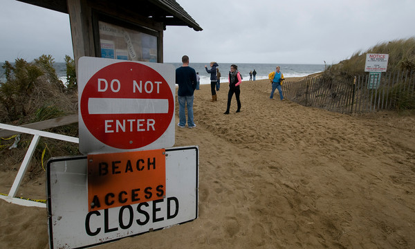 Newbury: People ignore signs on Plum Island to check out the high surf caused by the leading edge of Hurrican Sandy. Jim Vaiknoras/staff photo
