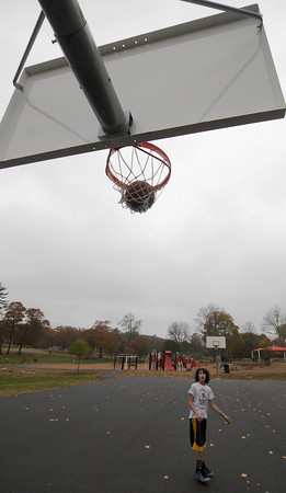 Amesbury: Noah Ferrandi, 13, watches as he swishes a shot at Amesbury Park. Noah wanted to shoot a few baskets before the storm hit. Jim Vaiknoras/staff photo