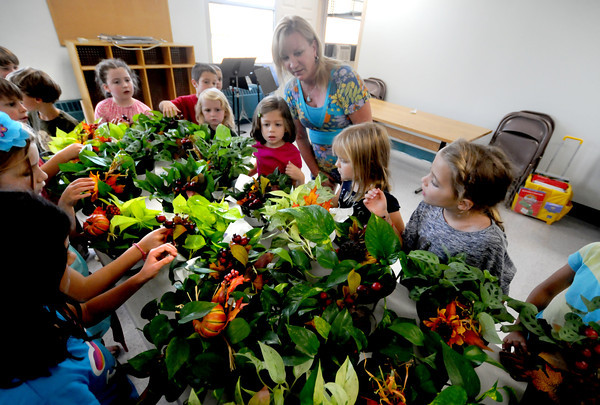 Wets Newbury: Susan Harvey owner of Susan's Interior Plantscaping, shows off some plants she is donating to teh Paige School in west Newbury to students in Cathy Madden's first grade class Friday. Harvey donated a plant for each class in the school to help with air quality and to teach the kids about taking care of plants. Jim Vaiknoras/staff photo