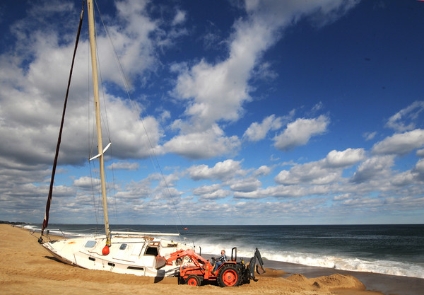 Newbury:Mike Goodridge of Tow/US removes sand from around a sailboat that beached on Plum Island Friday night. Jim Vaiknoras/staff photo