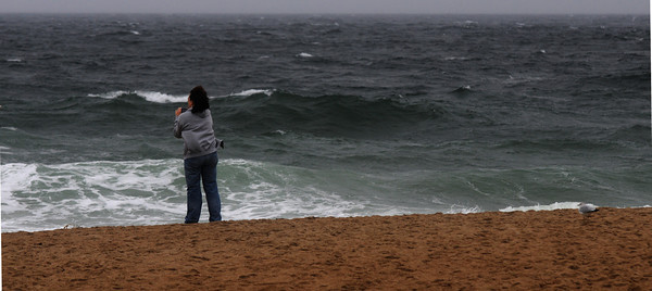 Salisbury: A woman uses her phone to take a few photos of the high surf on Salisbury Beach caused by teh leading edge of Hurrican Sandy. Jim Vaiknoras/staff photo