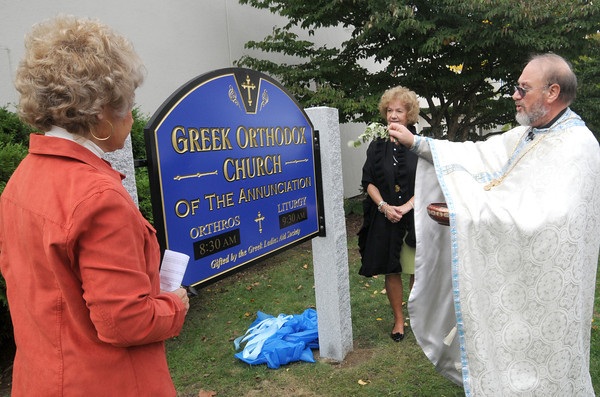 Newburyport: Father Constantine Newman blesses the new sign at The Greek Orthodox Church in Newburyport after it was unvailed by Irene Katsoulis , left and Dorothy Davis of the Greek Ladies Aid Society Sunday morning. The sign was donated by the society. Jim Vaiknoras/staff photo