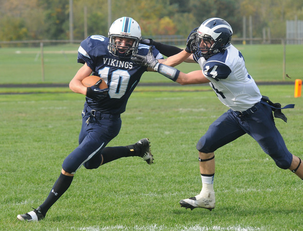 Byfield: Triton's Jake Gerninara stiff arms Swampscott's Devin Conroy during their game Saturday in Byfield. Jim Vaiknoras/staff photo