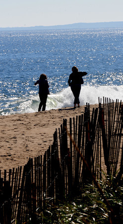 Newbury: Two women walk along a sunny Plum Island Beach Thursday afternoon. Jim Vaiknoras/staff photo