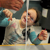 Salisbury: Emma Roy, 7, is amused as teacher Neale Dunn pours out a mixture of Elmer's Glue, borax and water which makes a Silly Putty-like substance when combined. They were at the Salisbury Elementary School afterschool program Explorations in the Mad Scientist Club unit and were learning yesterday about polymers. Bryan Eaton/Staff Photo
