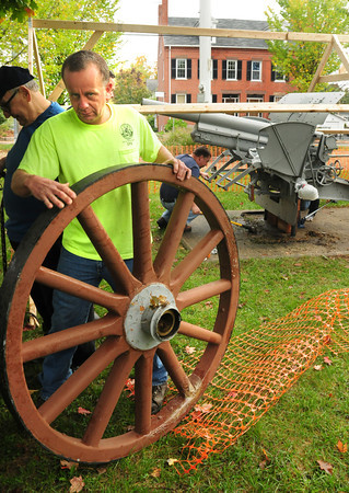 Newburyport: Lee Wilson of the Newburyport DPS removes one of two wheels from the 75 mm Howitzer at the Bartlet Mall which will repaired. Bryan Eaton/Staff Photo