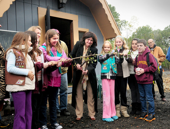 Newburyport: Newburyport Mayor Donna Holaday uses cutters to cut a branch during the opening of the new compost facility with girl scouts from Troop 60464. The girl scouts researched and prepared display materials for the education center in the back of photo.  Bryan Eaton/Staff Photo