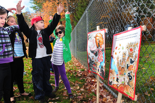 "Salisbury: Students at Salisbury Elementary School act out scenes from the book ""There Was An Old Lady Who Swallowed Some Leaves"" on Thursday on a Storywalk. The pages of the book are posted in different locations and the students walk to each of them to read to get some excercise instead of just turning the pages. Bryan Eaton/Staff Photo"