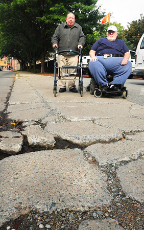 Newburyport: The cracked sidewalk outside Newburyport's Sullivan Building, which houses elderly residents, makes it difficult for those with disabilities as Francis Bradbury, left, and George Souther Jr. to get by with wheelchairs or walkers. Bryan Eaton/Staff Photo