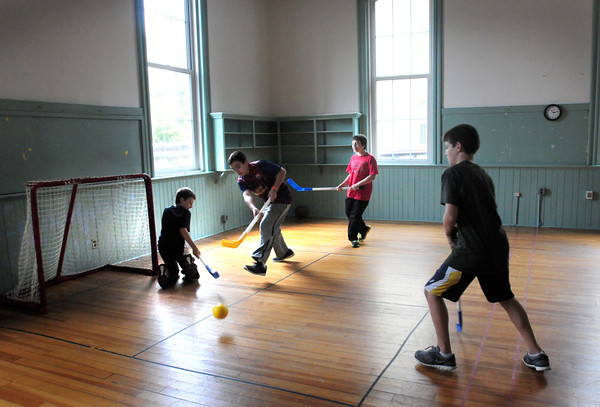 Newburyport: Youngsters play a game of floor hockey at the Kelley School Youth Center as the rain kept activities indoors. Rain is possible today and tomorrow with brightening for the first part of the weekend. Bryan Eaton/Staff Photo