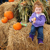 Newburyport: Vivan Bodycombe, 2, of Ipswich is in the middle of a fall scene as she found a comfy spot to eat her hot dog bun yesterday. She was visiting cousins in Newburyport and attended the Fall Harvest Festival in Market Square. Bryan Eaton/Staff Photo