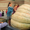 Newbury: Maggie Rand, left, and Jawzlyn Flanagan, both 9, feel the rough skin of a 1,256 pound pumpkin at Newbury Elementary School on Tuesday morning. George and Mary Ann Hoomis have a small farm in Ipswich and brought the gourd for children to learn about. Bryan Eaton/Staff Photo