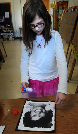 "Newburyport: Maddy Pitman, 8, checks out the collage she's working on of Bresnahan School principal Kristina Davis during art class. Children had their choice of Davis, or vice principal Karina Macia, to work on ""Face For a Base"" as they learned about collages. Maddy was working turning her collage into a teddy bear. Bryan Eaton/Staff Photo"