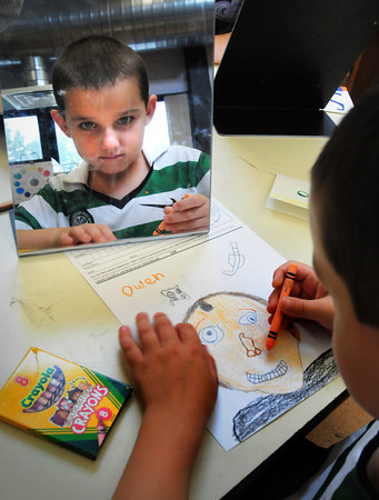 Amesbury: With the aid of a mirror, Owen Brannelly, 7, works on a self-portrait Monday afternoon. The first-grader at the Cashman School in Amesbury was in Karen Greenfield's art class. Bryan Eaton/Staff Photo