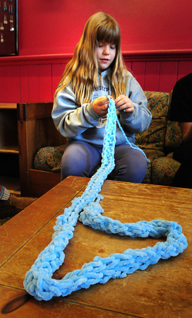 Newburyport: Michelle Gendron, 10, makes a scarf by finger knitting Monday afternoon. She was at the Kelley School Youth Center where some friends were knitting using the traditional needles. Bryan Eaton/Staff Photo