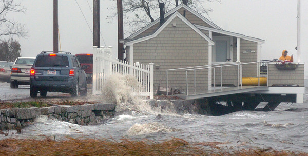 Newburyport: Storm-watchers pulled over on Water Street in Newburyport as waves splash onto the roadway at the old clam shack building. Bryan Eaton/Staff Photo