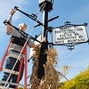 Amesbury: Dan Wilson, Jr. from Wilson Welding in Salisbury reinstalls the  road signs at the roundabout in Amesbury's Market Square on Tuesday morning. Paid for by the Amesbury Rotarian Club, the company refabricated new frames and sandblasted the signs and gave them a fresh coat of paint. Bryan Eaton/Staff Photo