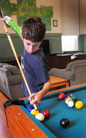 Newburyport: Despite breaking his hand as he hit his hand on an armrest at home, Andrew Moreland, 12, made some decent shots in pool. He was shooting with his friend Jason Howes, 12, at the Kelley School Teen Center. Bryan Eaton/Staff Photo