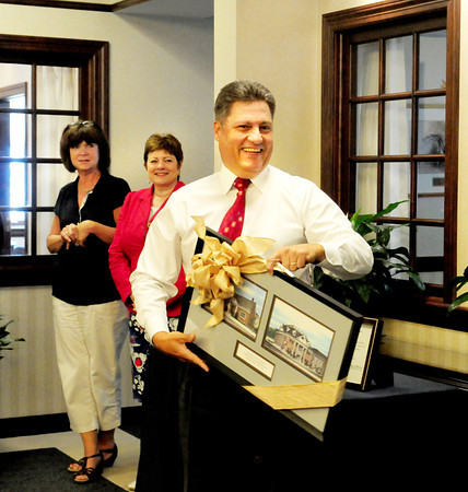 Georgetown: Georgetown Savings Bank president Robert E. Balletto smiles after receiving framed prints of the bank as he was honored for his 30 years of service with the bank. Bryan Eaton/Staff Photo