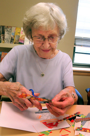 "Amesbury: Ida Phillips uses pieces of gift wrap and other leftover pieces of paper to create ""iris folding"" which originated in Holland and uses pieces of paper starting in the center and circling out as in the iris of a camera. She was at the Amesbury Senior Center on Thursday morning. Bryan Eaton/Staff Photo"