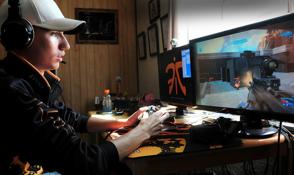 Salisbury: Justin Saboo plays a video game with team members remotely at his Salisbury home. The professional video game player will be appearing on a reality show called The Controller: Medal of Honor Warfighter. Bryan Eaton/Staff Photo