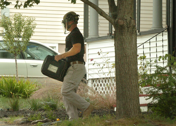 Amesbury: A trooper with the Mass. State Police Bomb Squad carries a World War II hand grenade, in a protective case, found on Carpenter Street in Amesbury yesterday afternoon. Bryan Eaton/Staff Photo