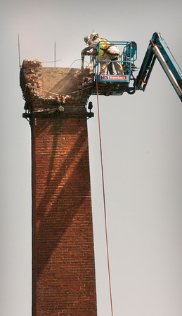 Newburyport: Workers demolish the top of the smoke stack at the Anna Jaques Hospital on Monday morning. They're removing the bricks down by jackhammer until about half way when heavy equipment will be used to knock the remaining structure down. Bryan Eaton/Staff Photo