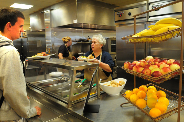 Newburyport: Matt Canning waits in line as head cook Eileen McConologue serves other students in view of apples, bananas and oranges in the Newburyport High School cafeteria. There were also side options to their meals on Wednesday such as carrot sticks, grapes and a bean salad. Bryan Eaton/Staff Photo