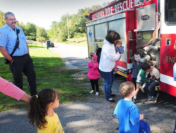 Salisbury: Salisbury fire Lt. David Doyle looks on as children check out a fire engine on Tuesday. The Salisbury Day Care Support Group, a group of local child care providers from Salisbury, who in a combined effort with the Salisbury Fire Department and E.S.C.A.P.E program (a non-profit fire education program with founders from the Merrimac Fire Department) came together to educate young children in Fire Prevention and Fire Safety Awareness. Bryan Eaton/Staff Photo
