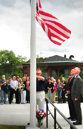 Amesbury: Commander Bob Smith of VFW Post 2016 raises the flag during a ceremony dedicating the flagpole to Jordan Shay, an Amesbury soldier who died in Iraq. Bryan Eaton/Staff Photo