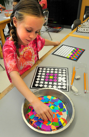 Salisbury: Ava Hovee, 7, chooses from colorful squares as she constructs mozaics in Amy Merluzzi's art class at Salisbury Elementary School on Monday. The children are learning about patterns, symmetry and matching opposite colors. Bryan Eaton/Staff Photo