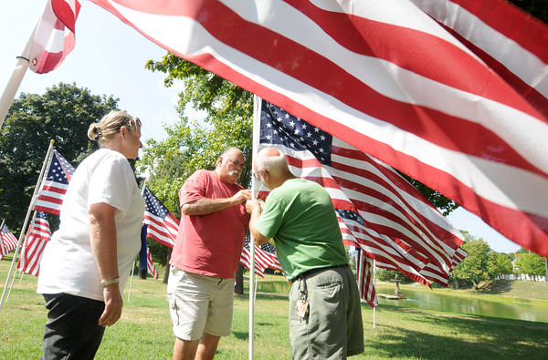 Newburyport Anthony Fusco attached tag honoring Michael Drago with some help from  Ben Iaconoand  Exchange Club president Pat Zalewski at teh Field of Honor on the Bartlet Mall. Jim Vaiknoras/staff photo