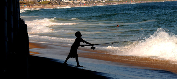 Salisbury: Bobby Doonan, 7, tries his luck fishing in the surf at salisbury Beach Saturday. Jim Vaiknoras/staff photo