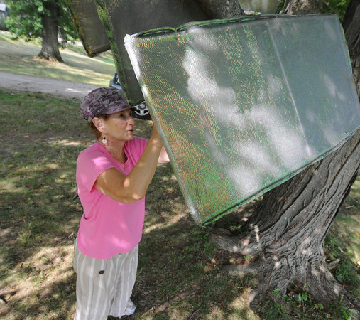 "Newburyport: Muriel Angelil installs her sculpture "" Are they Chairs"" at Maudslay Saturday. Jim Vaiknoras/staff photo"