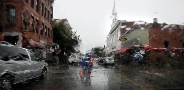 Newburyport: A family rushes across a rain soaked Pleasent Street in Neburyport Sunday morning. Jim Vaiknoras/staff photo