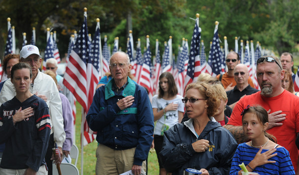 Attendees at the Field of Honor Dedication on the Bartlet Mall in Newburyport Sunday cover their heart as they recite the Pleadge of Allegiance . JIm Vaiknoras/staff photo