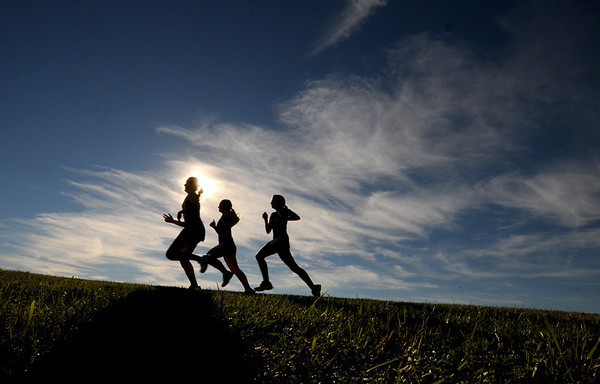 Byfield: Three female runners are silhouetted against the September sky  quad cross country meet at Triton Wednesday . Jim Vaiknotas/staff photo