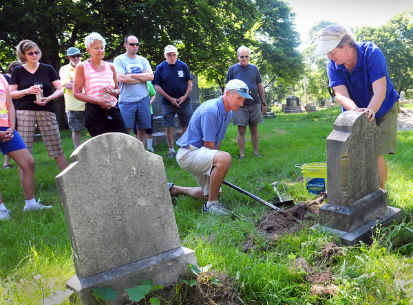 Newburyport: Ghlee Woodworth, right, led The Cemetery Crawl giving tours and history highlights of the Old Burying Ground and Highland Cemetery. Here she demonstrates how she and other volunteers have been repairing gravestones in disrepair. Bryan Eaton/Staff Photo