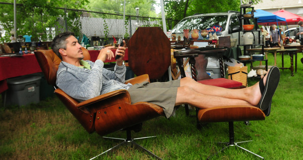 Newburyport: Peter Mack of Ould Newbury Antiques sits on some of his merchandise while waiting for customers at the 49th Antique Show and Sale at the Belleville Congregational Church. Bryan Eaton/Staff Photo