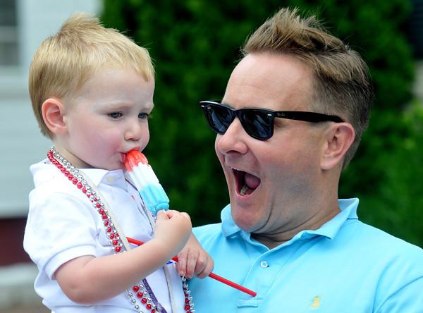 Newburyport: Parker Jackman , 2, enjoys a Rocket Pop with his dad Ken at the Yankee Homecoming Parade Sunday. Jim Vaiknoras/staff photo
